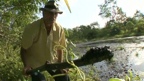 Greg Palast holds up crude oil residue poisoning the water supply of the Cofan Indians in Ecuador (Greg Palast)