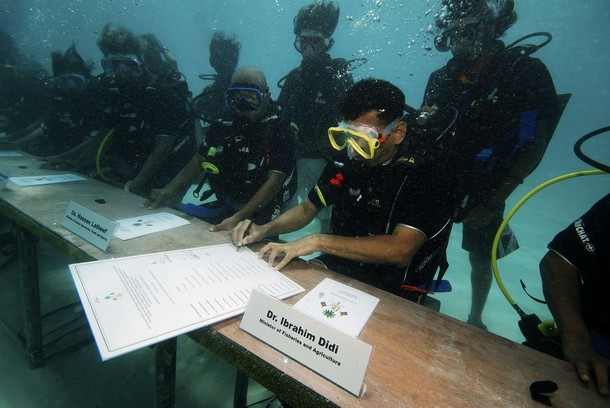 "Sitting 1.5 meters deep in the lagoon, the cabinet ministers and secretaries used hand signals and a white board to communicate. The meeting concluded when members of the cabinet signed a declaration calling on all nations to ""join hands and reduce carbon emissions and bring down the level of carbon in the atmosphere to below 350 ppm""."