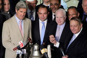 Senators John Kerry (left) and John McCain (third from left) ring the bell to pen the Cairo stock exchange market on June 26, 2011 (Amr Nabil/AP)