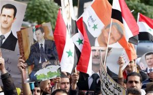 Supporters of Syrian President Bashar al-Assad outside the Foreign Ministary in Damascus (Louai Beshara/AFP/Getty Images)