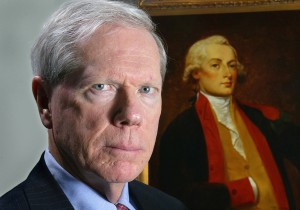 Paul Craig Roberts in front of a portrait of Alexander Hamilton, the first Secretary of the Treasury.