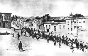 Armenians are marched to a nearby prison in Mezireh by armed Turkish soldiers. Kharpert, Armenia, Ottoman Empire, April, 1915 (Public Domain)