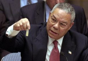 At the UN, Colin Powell holds a model vial of anthrax, while arguing that Iraq is likely to possess WMDs. 5 February 2003. (Wikimedia Commons)