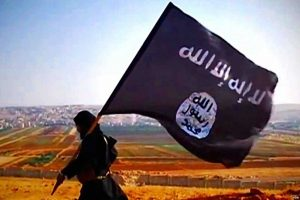 A militant carries the flag of the Islamic State, or ISIS (VOA)